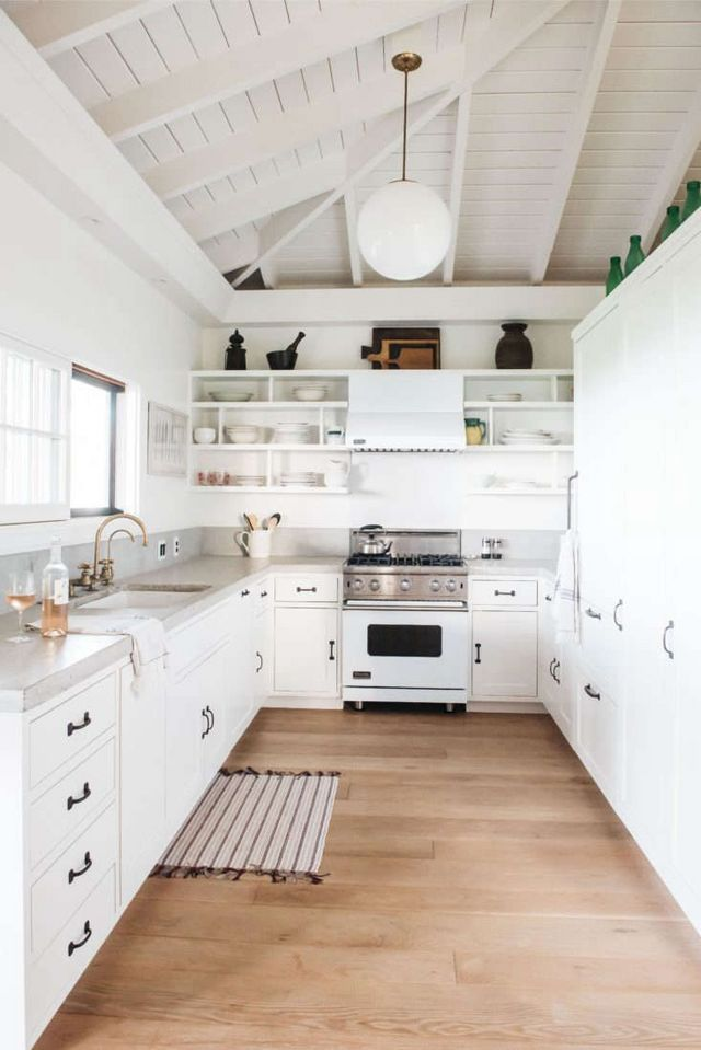 The Main Houses Slender All White U Shaped Kitchen Is At Once Modern And Retro With Concrete Counters Globe Lights American Pottery